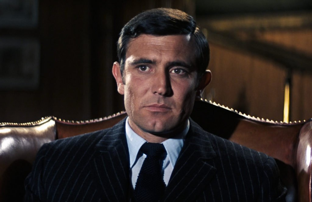 Bond wears a navy chalk stripe suit to the office in On Her Majesty's Secret Service