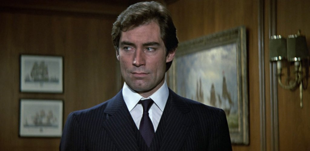 Timothy Dalton wears a navy suit with grey chalk stripes in The Living Daylights