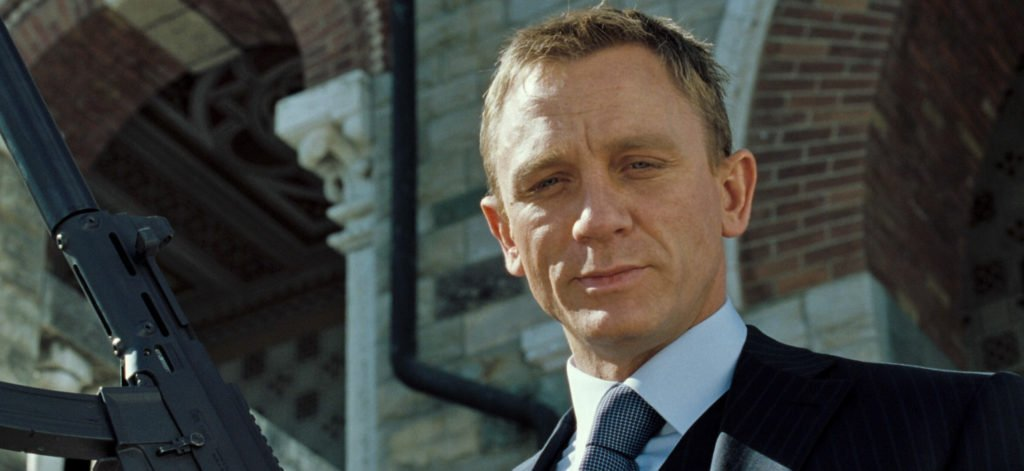 Daniel Craig wears a navy suit with track stripes in Casino Royale