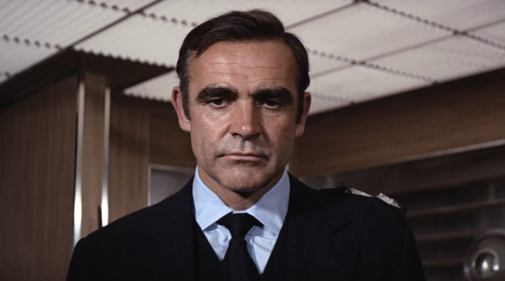 Sean Connery wear a navy suit with blue chalk stripes in Diamonds Are Forever