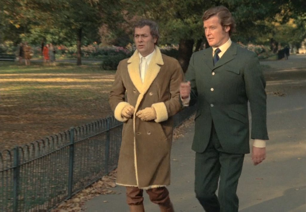 Cyril Castle made Roger Moore's high button three suit in The Persuaders. It has a slanted, flapped breast pocket and flared link-button cuffs.